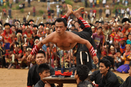 Mon, Nagaland - April 2012: Native boys carry man lying on four large spikes during performance at Aoleang festival in Mon, Nagaland. This festival showcases rich cultural heritage of this country. Documentary editorial.