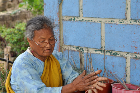 roo: Cherapunjee, Meghalaya - March 2012: Photo of old native woman with glasses and yellow scarf working in front of her house near Cherapunjee in Meghalaya, place where Indian rubber tree with incredibly strong root system thrives and forms famous living roo