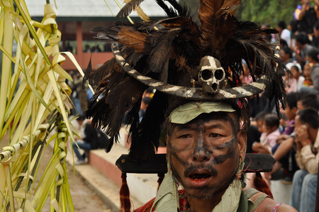 nagaland: Mon, Nagaland - April 2012: Native man with black colour on his face wears hat with black and orange feathers and with small skull and bone in front during performance at Aoleang festival in Mon, Nagaland. Documentary editorial.