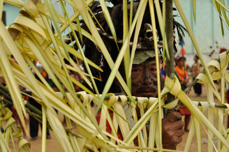 Mon, Nagaland - April 2012: Native man with black colour on his face and with big hat made of black feathers and skull with bone looks to photocamera through yellow cloth on construction during performance at Aoleang festival in Mon, Nagaland.  Aoleang is