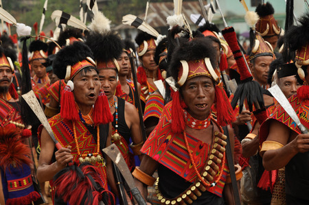 Mon, Nagaland - April 2012: Crowd of native men in costumes and hats hold rifles in their hands and sing during performance at Aoleang festival in Mon, Nagaland. Aoleang is biggest and most significant festival of Konyak Nagas of Nagaland. Documentary edi