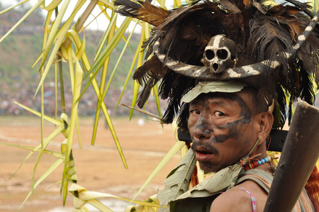 Mon, Nagaland - April 2012: Native man with big hat made of black feathers and skull with bone looks over his shoulder to photocamera during performance at Aoleang festival in Mon, Nagaland.  Aoleang is biggest and most significant festival of Konyak Naga