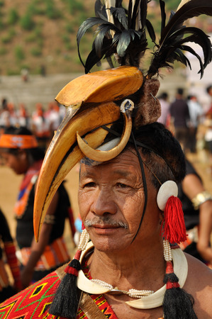 documentary: Mon, Nagaland - April 2012: Native man poses with beak-like hat with black feathers at top at Aoleang festival in Mon, Nagaland. This festival showcases rich cultural heritage of this country. Documentary editorial.