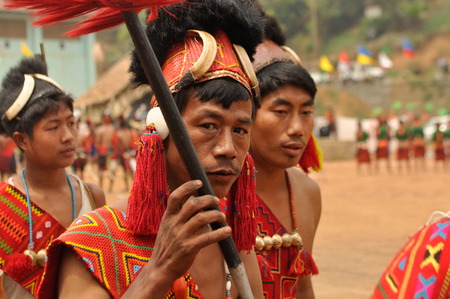 nagaland: Mon, Nagaland - April 2012: Native man in traditional colourful costume and hat with fur and bones holds wooden stick and looks to photocamera during performance at Aoleang festival in Mon, Nagaland.  Aoleang is biggest and most significant festival of Ko
