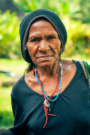 frowns: Sara village, Papua New Guinea - July 2015: Native woman dressed in black shirt with black cap wears necklace made of beads and frowns to photocamera at Sara village in Papua New Guinea. Documentary editorial. Editorial