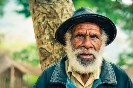 frowns: Kubor Range, Papua New Guinea - July 2015: Old man with white beard wears black hat and black jacket and frowns to photocamera in Kubor Range, Papua New Guinea. Documentary editorial.