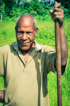 wooden stick: Palembe, Papua New Guinea - July 2015: Older native man in yellow shirt holds wooden stick and poses on green field in Palembe, Sepik river, Papua New Guinea. Documentary editorial.