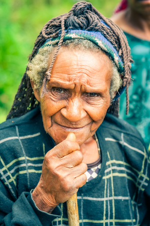 frowns: Sara village, Papua New Guinea - July 2015: Old woman with wrinkles in black and yellow shirt holds wooden stick and frowns to photocamera at Sara village in Papua New Guinea. Documentary editorial.