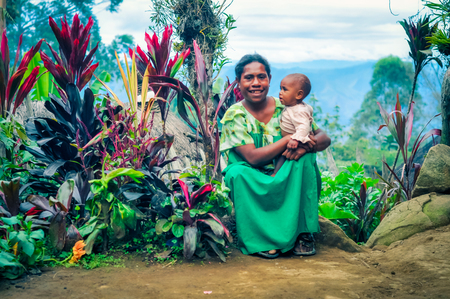 Sara village, Papua New Guinea - July 2015: Woman in green dress sits on stone and smiles to photocamera with her child in her arms surrounded by beautiful flora of this region at Sara village in Papua New Guinea. Documentary editorial. Editorial