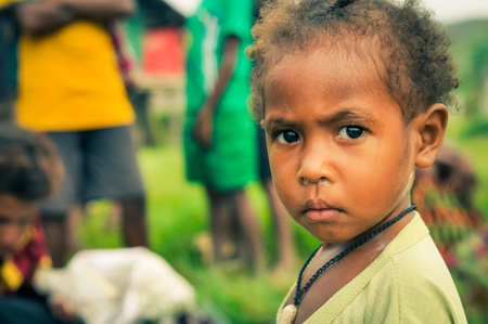 frowns: Palembe, Papua New Guinea - July 2015: Small child in yellow shirt with beautiful black eyes frowns to photocameras in Palembe, Sepik river, Papua New Guinea. Documentary editorial. Editorial