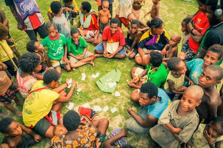 sitting on the ground: Palembe, Papua New Guinea - July 2015: Native children sit on ground in circle and play cards in Palembe, Sepik river, Papua New Guinea. Documentary editorial.