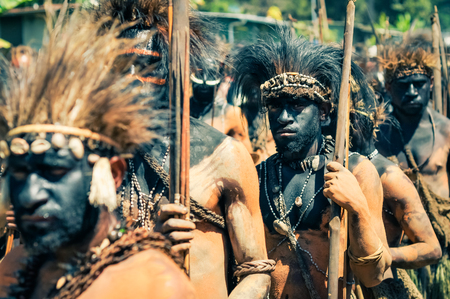 headbands: Wabag, Pap�a Nueva Guinea - Agosto 2015: Native hombres medio desnudos con color negro en las caras y las cintas para la cabeza con plumas tienen palos de madera y de pie en la fila durante la presentaci�n tradicional Enga cultural en Wabag, capital de la provincia de Enga, Pap�a Nueva Guinea. Documental