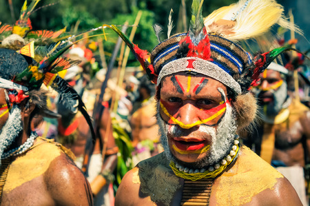 Wabag, Papua New Guinea - August 2015: Native bearded man with necklace, headband and cap with feathers with face covered in red and yellow colours poses and looks to photocamera during Enga cultural show in Wabag, capital of Enga Province, Papua New Guin