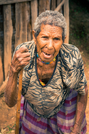 wooden stick: Kubor Range, Papua New Guinea - August 2015: Old native woman in colourful skirt and black and brown shirt holds wooden stick and poses to photocamera in Kubor Range, Papua New Guinea. Documentary editorial.