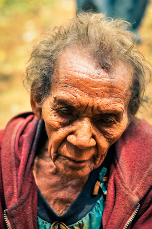 difficult lives: Kubor Range, Papua New Guinea - August 2015: Old native woman with wrinkles dressed in red sweatshirt looks sadly down in Kubor Range, Papua New Guinea. Documentary editorial. Editorial