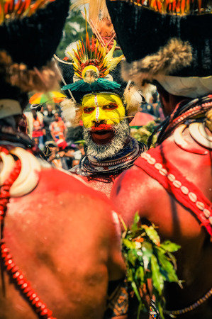 frowns: Wabag, Papua New Guinea - August 2015: Native man with yellow and red colour on his face wears hat made of plants and fur and many necklaces made of beads and frowns to photocamera with typical pierced nose during performance at traditional Enga cultural