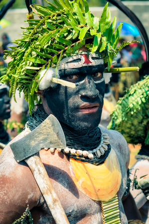 Wabag, Papua New Guinea - August 2015: Native man with face covered in black and white colour wears green hat made of leaves of plant and black necklace and holds axe during traditional Enga cultural show in Wabag, capital of Enga Province, Papua New Guin