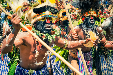rhythms: Wabag, Papua New Guinea - August 2015: Native half-naked men with large caps made of feathers and fur have colour on their faces and dance to typical rhythms with wooden sticks in their hands during traditional Enga cultural show in Wabag, capital of Enga