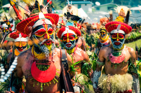 cintillos: Wabag, Papua New Guinea - August 2015: Native half-naked people in colourful costumes with large red caps with feathers and headbands and with large necklaces dance and pose to photocamera during traditional Enga cultural show in Wabag, capital of Enga Pr