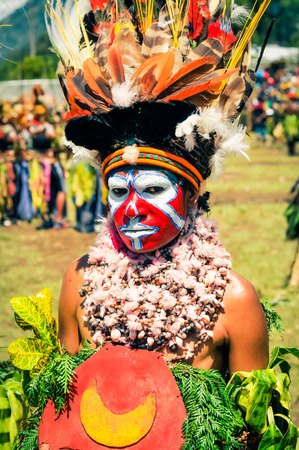 tr: Wabag, Papua New Guinea - August 2015: Photo of native half-naked woman dressed in traditional costume with beautiful hat made of colourful feathers and many necklaces made of stones with colours on her face looking to photocamera during performance at tr