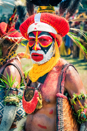 frowns: Wabag, Papua New Guinea - August 2015: Native man in colourful costume with large hat with feathers and colours on face poses and frowns to photocamera during traditional Enga cultural show in Wabag, capital of Enga Province, Papua New Guinea. Documentary