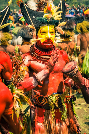rhythms: Wabag, Papua New Guinea - August 2015: Native half-naked man with red and yellow colours on his face and body wears large hat with feathers , many necklaces and plants on his arms and plays drum to rhythms of typical music during performance at traditiona Editorial