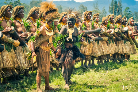 Wabag, Papua New Guinea - August 2015: Native barefoot women and man in traditional costumes with caps and skirts and grass stand in row and play drums during performance at traditional Enga cultural show in Wabag, capital of Enga Province, Papua New Guin