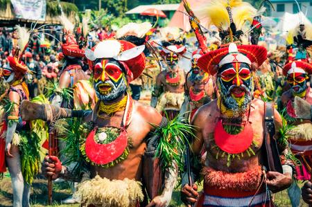 headbands: Wabag, Pap�a Nueva Guinea - Agosto de 2015: personas semidesnudas nativos en trajes de colores con grandes gorras rojas con plumas y cintas para la cabeza y con grandes collares de bailar durante la demostraci�n tradicional Enga cultural en Wabag, capital de la provincia de Enga, Pap�a Nueva Guinea