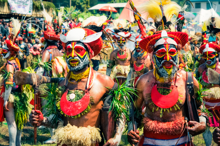 cintillos: Wabag, Papua New Guinea - August 2015: Native half-naked people in colourful costumes with large red caps with feathers and headbands and with large necklaces dance during traditional Enga cultural show in Wabag, capital of Enga Province, Papua New Guinea