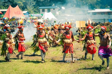cintillos: Wabag, Papúa Nueva Guinea - Agosto de 2015: los hombres medio desnudos nativos en trajes de colores con grandes gorras rojas con plumas y cintas para la cabeza de pie en la fila y la danza tradicional durante la presentación de Enga cultural en Wabag, capital de la provincia de Enga, Papúa Nueva Guinea. Documenta Editorial