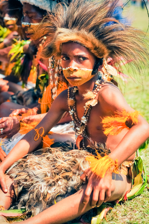 frowns: Hagen show, Papua New Guinea - circa August 2015: Small native boy in traditional costume made of feathers sits on ground and frowns during Hagen show, Papua New Guinea. Documentary editorial.
