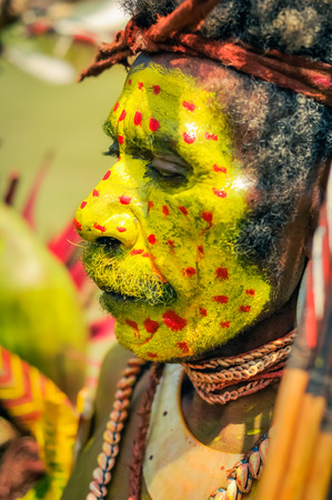 face covered: Hagen show, Papua New Guinea - circa August 2015: Old native man with moustache and face covered in yellow colour with red dots during Hagen show, Papua New Guinea. Documentary editorial. Editorial