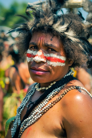 frowns: Hagen show, Papua New Guinea - circa August 2015: Half-naked woman with white and red colour on face wears hat made of beads and frowns during Hagen show, Papua New Guinea. Documentary editorial.