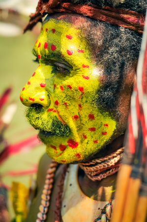 face covered: Hagen show, Papua New Guinea - circa August 2015: Old native man with moustache and face covered in yellow colour with red dots poses during Hagen show, Papua New Guinea. Documentary editorial.