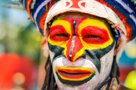 frowns: Hagen show, Papua New Guinea - circa August 2015: Native man with bright colours on his face wears knitted cap and frowns during Hagen show, Papua New Guinea. Documentary editorial.