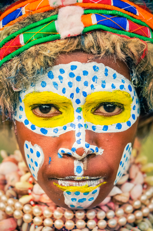 frowns: Hagen show, Papua New Guinea - circa August 2015: Young native girl with colours on her face and frowns during Hagen show, Papua New Guinea. Documentary editorial.