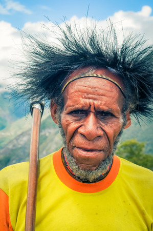 dani: Dani circuit, Indonesia - September 2015: Old bearded man in yellow shirt holds axe on his shoulder and frowns in beautiful region in Dani circuit near Wamena, Papua, Indonesia. Documentary editorial. Editorial