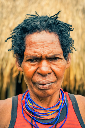 dani: Dani circuit, Indonesia - September 2015: Older native woman dressed in orange shirt posing and frowning in Dani circuit near Wamena, Papua, Indonesia. Documentary editorial.
