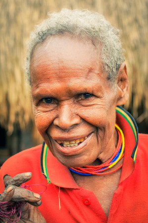 dani: Dani circuit, Indonesia - September 2015: Old native woman with colourful necklaces made of beads poses and smiles happily in Dani circuit near Wamena, Papua, Indonesia. Documentary editorial.