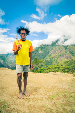 dani: Dani circuit, Indonesia - September 2015: Old native man in yellow shirt holds axe on his shoulder in Dani circuit near Wamena, Papua, Indonesia. Documentary editorial.