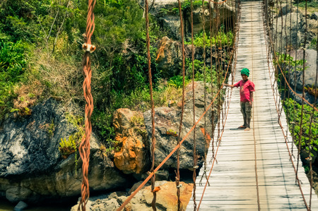 dani: Dani circuit, Indonesia - September 2015: Small native boy dressed in red shirt and green cap stands on wooden bridge in Dani circuit near Wamena, Papua, Indonesia. Documentary editorial. Editorial