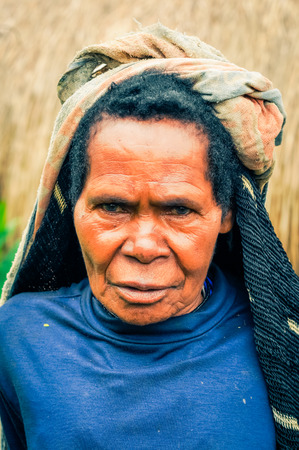 dani: Dani circuit, Indonesia - September 2015: Old native woman dressed in blue shirt with headcloth poses and frowns in Dani circuit near Wamena, Papua, Indonesia. Documentary editorial.