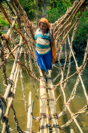 headcloth: Trikora, Indonesia - September 2015: Old native barefoot woman stands on wooden bridge over river in Trikora, Papua, Indonesia. Documentary editorial. Editorial