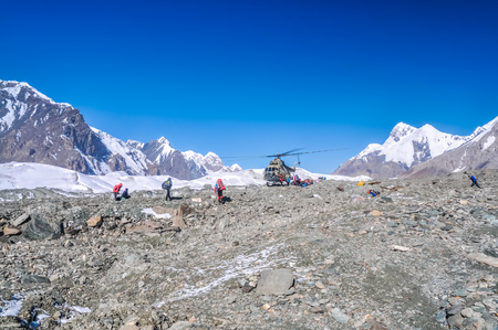 glaciar: Photo of helicopter and hikers on rocky terrain surrounded by mountains near South Inylcheck Glaciar in Kyrgystan.