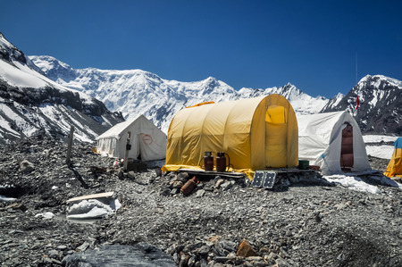 glaciar: Tents of hikers on rocky ground surrounded by mountain range near South Inylcheck Glaciar in Kyrgystan.