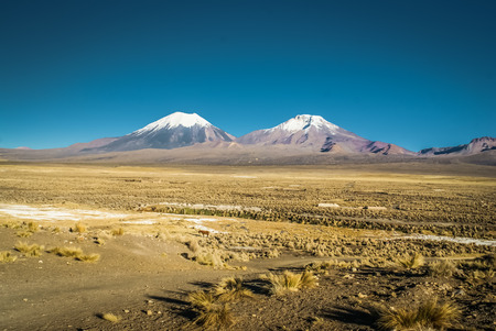 Photo of lonely wilderness and mountains with snow in Parque Nacional Sajama in Bolivia, South America.
