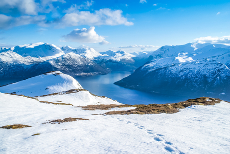 Photo of mountain range covered in snow and river in distance in Volda in Norway. Stock Photo