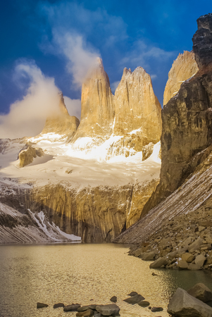 Photo of river and rocks covered in snow in Parque Nacional Torres del Paine in Chile.