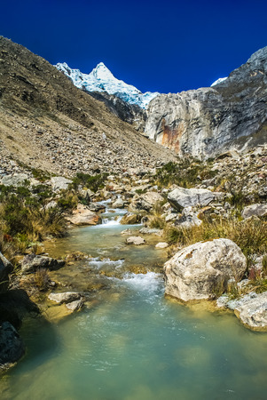 Photo of Alpamayo, peak in Cordillera Blanca of Peruvian Andes and river in Parque Nacional Huascaran in South America. Stock Photo
