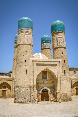 Photo of large house with typical roof and towers with blue tops in Buchara in Uzbekistan.